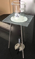 Bunsen burner set up with tripod, gauze mat with ceramic centre and glass beaker.