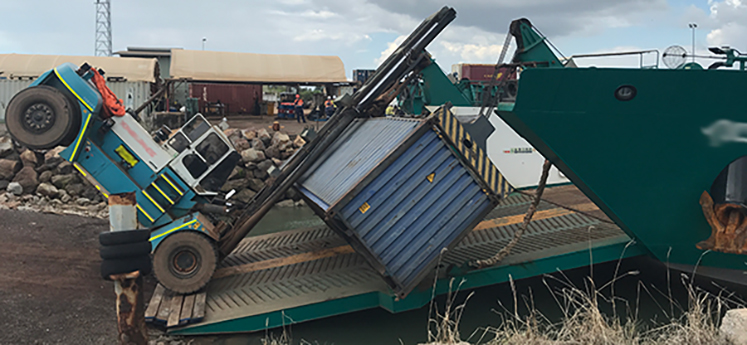 The image shows a 37 tonne forklift carrying a shipping container, tipped forward onto the bow ramp of a vessel.