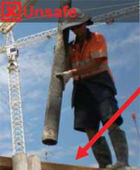 Image shows a construction worker holding a concrete hose standing next to an unprotected edge