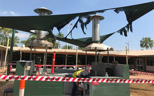 The image shows the in built barbecue for incident 2. Red hazard tape surrounds the barbecue area. The shade cloth above the barbecue area has been burnt. A one meter high wall almost encloses the barbecue area.