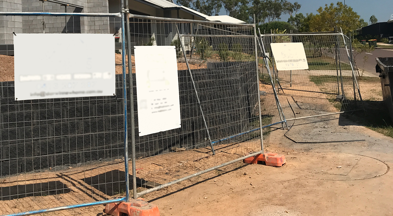 The image shows temporary fencing at a building site. Two fence panels are not attached tot he rest of the fence and are leaning against a retaining wall, providing very little site security.