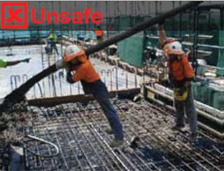 Image show two construction workers stretching a delivery hose