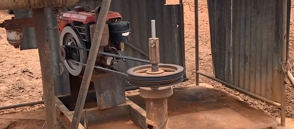 The image shows a bore pump with the moving pulleys and belt unguarded. (Source: NT Police)